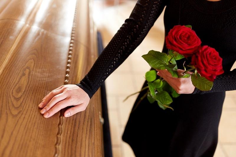 Frau mit roter Rose am Sarg