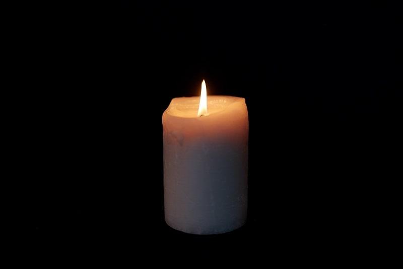 Kerze brennt vor schwarzem Hintergrund-min